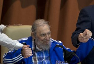 FILE - In this April 19, 2016 file photo, Fidel Castro sits as he clasps hands with his brother, Cuban President Raul Castro, right, and second secretary of the Central Committee, Jose Ramon Machado Ventura moments before the playing of the Communist party hymn during the closing ceremonies of the 7th Congress of the Cuban Communist Party, in Havana, Cuba. Castro has died at age 90. President Raul Castro said on state television that his older brother died late Friday, Nov. 25, 2016. (Ismael Francisco/Cubadebate via AP)